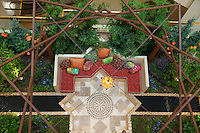 "A garden bench sits amid water features and lush foliage with a large wooden framework providing vertical detail.  The Orange Coast College Hotriculture Club entered the 2011 Spring Garden Show landscape design competition (http://www.springgardenshow.com/) and won first place in the student category for their ""Moorish Flourishes in a Contemporary Garden"" design."