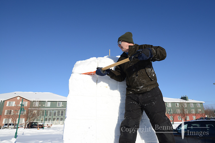 Guy Urban takes advantage of the bright winter sun to begin work on his snow sculpture, one of the premier events of the Anchorage, Alaska, Fur Rendezvous winter carnival in February, 2013.