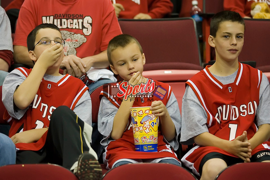 A trio of young Davidson Wildcat fans enjoy some popcorn prior to the game vs. the Gonzaga Bulldogs in the first round of the 2008 NCAA Men's Basketball Championship at the RBC Center in Raleigh, NC, Friday, March 21, 2008.
