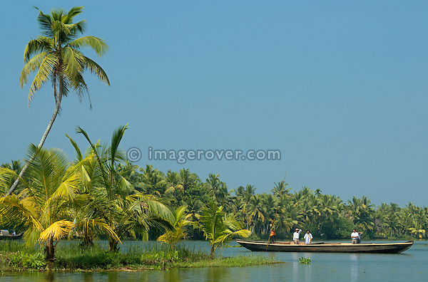 India, Kerala, backwaters. Indian boatman with a punt pole shipping people across the Backwaters.