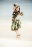 Woman dances hula at Kailua Beach in  ti leaf skirt and leis. Oahu