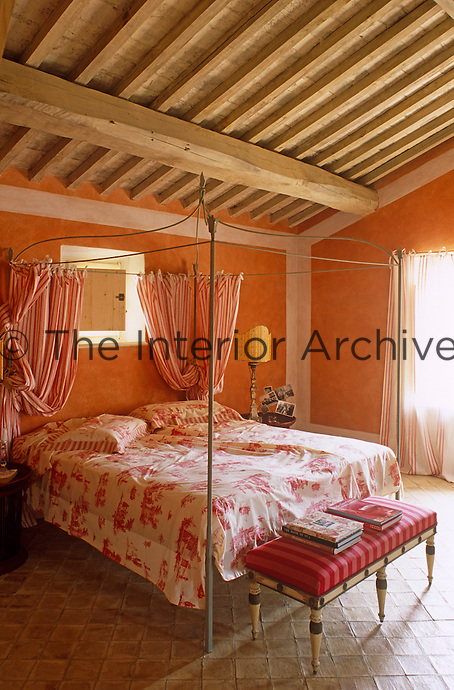 Beneath the beamed ceiling of this bedroom stands a  wrought-iron four-poster bed with toile de Jouy sheets