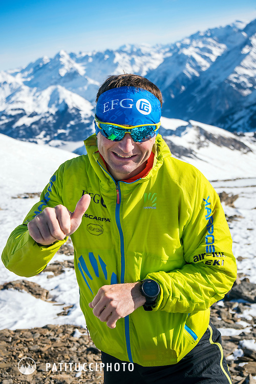 Ueli Steck using ski mountaineering for training above Grindelwald, Switzerland. Ueli has stopped to look at his watch.