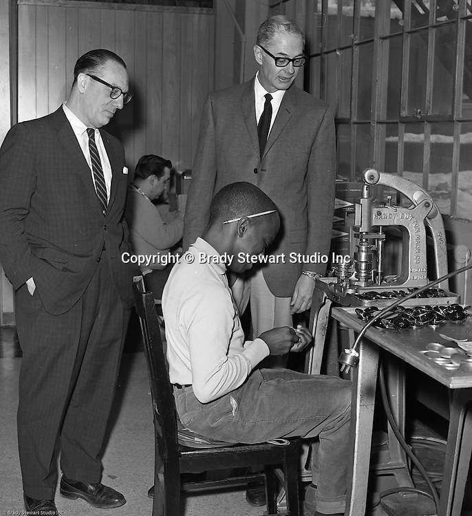 Pittsburgh PA:  Bob Prince touring the Goodwill Industries facility and talking with a young man using a stamping machine- 1966.  <br /> In 1966, Goodwill Industries was part of the United Fund Community Chest Agency which eventually became the United Way of Allegheny County in 1974. Goodwill Industries provides a broad array of employment-related education and workforce development programs and services for people with physical and intellectual disabilities and other barriers to employment.