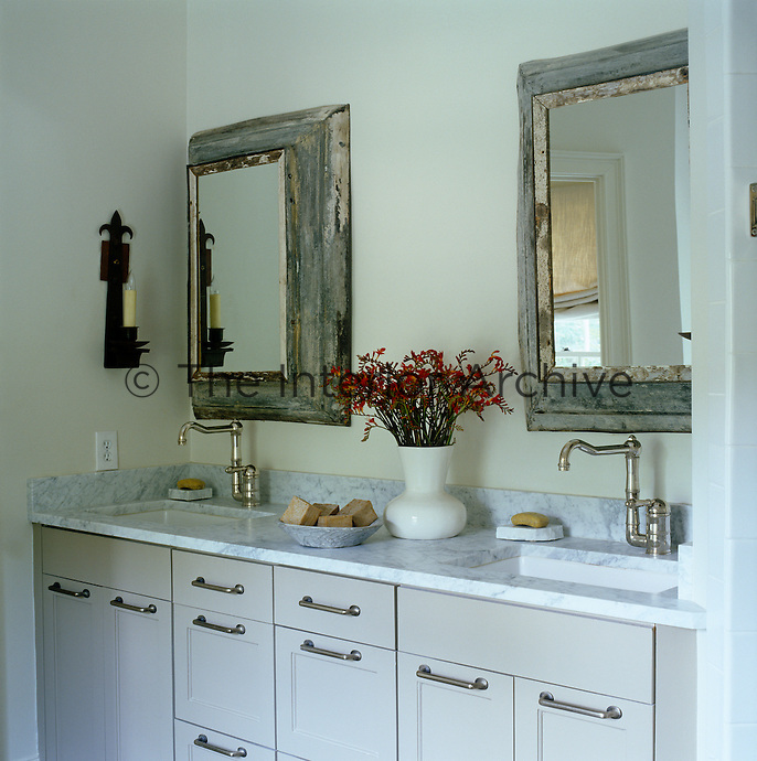 A pair of mirrors in distressed wooden frames hangs above a marble-topped bathroom unit with twin basins