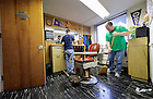 "Feb. 12, 2013; Seminarian Anthony Stachowski (right) sweeps up his own hair after receiving a haircut from fellow seminarian Chase Pepper in the Moreau Seminary barber shop.  The job of seminary barber is handed down from seminarian to seminarian.  There is a nominal charge of $5 for the service. ""Saint André Bessette was a barber,"" noted Pepper...Photo by Matt Cashore/University of Notre Dame"