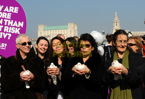 Annie Lennox, Cherie Lunghi and Bianca Jagger.Photocall ahead of a march in aid of International Women's Day at the Millenium Bridge, London, England. .March 8th, 2011.half length black coat jacket sunglasses shades white dove bird holding carrying .CAP/CJ.©Chris Joseph/Capital Pictures.