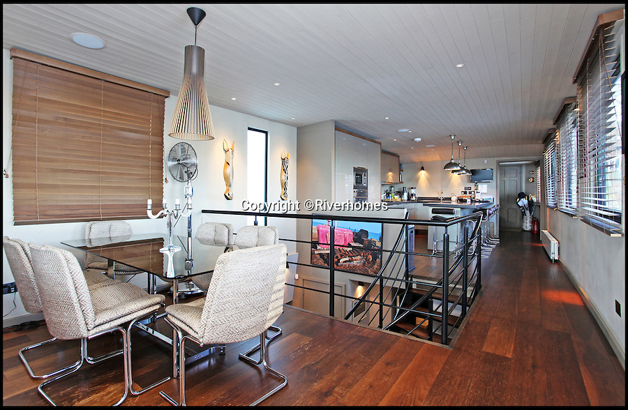 BNPS.co.uk (01202 558833)<br /> Pic: Riverhomes/BNPS<br /> <br /> Kitchen/Dining area.<br /> <br /> Heart of Lightness - Tardis like houseboat on the Thames.<br /> <br /> A houseboat that looks more like a luxurious penthouse suite inside has gone on the market for a whopping &pound;1.5 million - because it's in one of London's most exclusive locations.<br /> <br /> The 100ft vessel was once a former Dutch barge taking supplies up and down the Thames until it was retired from service in the 1960s and left to rot.<br /> <br /> But a decade later it was salvaged and turned into a houseboat before undergoing a complete refurbishment four years ago and moved to a premier mooring alongside one the swankiest addresses in the city.<br /> <br /> The plush houseboat, berthed at the entrance to Cheyne Walk, now boasts a lavish living room, stylish 50ft-long kitchen, a spiral staircase, two opulent bedrooms, three bathrooms and even a sun terrace.<br /> <br /> And despite its eye-watering &pound;1.5m asking price, experts at Riverhomes estate agents say the houseboat is actually a bargain and that anyone wanting to live in such luxury in the heart of Chelsea would have to shell out many millions more.