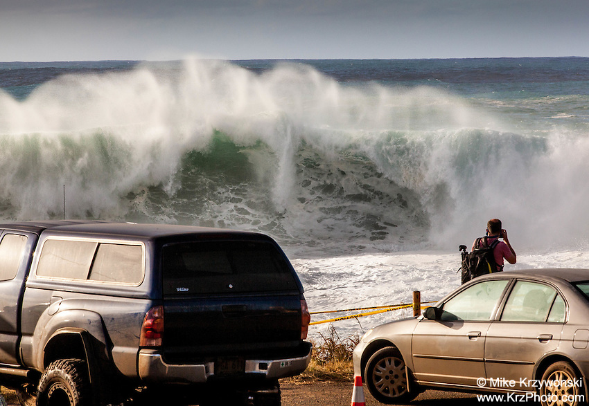 Spectator watching giant waves during a large winter swell at Shark's Cove, North Shore, Oahu