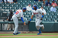 Buffalo Bisons manager Bobby Meacham (10) slaps hands with Socrates Brito (51) as he rounds third base after hitting a home run against the Caballeros de Charlotte at BB&T BallPark on July 23, 2019 in Charlotte, North Carolina. The Bisons defeated the Caballeros 8-1. (Brian Westerholt/Four Seam Images)