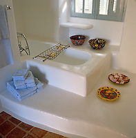 Colourful local bowls and plates surround this sunken bath
