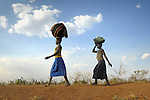 Women walking home near the Namokora camp for internally displaced persons. Two decades of war in northern Uganda have left almost two million people displaced, though progress in peace talks in 2006 initiated a small movement to return to home villages.