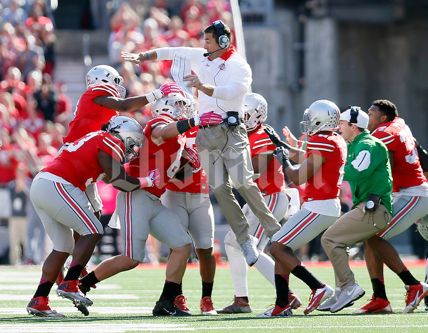 Ohio State Buckeyes co-defensive coordinator Luke Fickell jumps into the arms of Ohio State Buckeyes defensive end Sam Hubbard (6) after Hubbard make a interception against Maryland Terrapins offensive in the fourth quarter of their game in Ohio Stadium on October 10, 2015.  (Dispatch photo by Kyle Robertson)