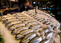 A worker inspects the salmon on sale at Pike Place Market in Seattle Washington.