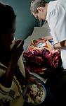 Foto: VidiPhoto..MASVINGO - Topdrukte in het missieziekenhuis Morgenster in Masvingo Zimbabwe. Omdat er nauwelijks medicijnen voorhanden zijn en veel staatsziekenhuizen nog plat liggen vanwege stakingen, krijgen de missieziekenhuizen in Zimbabwe te maken met een enorme golf aan patiënten uit de wijde regio. Zo ook het missieziekenhuis Morgenster bij Masvingo, dat gerund wordt door de Nederlandse arts Herman ten Hove. Het ziekenhuis wordt onder meer financieel gesteund door de Nederlandse zendingsorganisatie GZB. Foto: Dokter Herman ten Hove onderzoekt een baby.