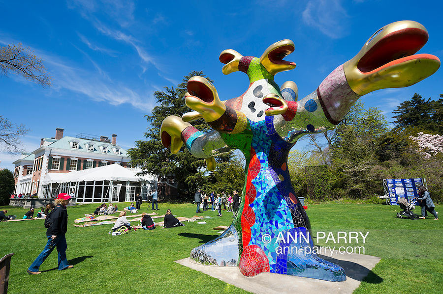 Roslyn Harbor, New York, USA. 21st April, 2013. At Celebrate Earth Day at Nassau County Museum of Art, children paint pictures on large rolls of paper on lawn near SNAKE TREE, a colorful, large mixed media sculptural installation by Niki de Saint Phalle.