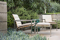 A pair of contemporary wood and metal garden chairs on part of the terrace surrounded by lush foliage