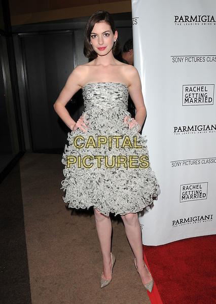 """ANNE HATHAWAY (wearing Oscar de la Renta).The Sony Pictures Classics L.A. Premiere of """"Rachel Gettig Married"""" held at The WGA Theatre in Beverly Hills, California, USA..September 15th, 2008                                                                     .full length strapless white grey gray print dress gold pointy shoes heels ruffled ruffles frills hands on hips .CAP/DVS.©Debbie VanStory/Capital Pictures."""