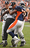 An official attempts to break up a skirmish between Jacksonville Jaguars fullback #33 Greg Jones and Denver Broncos linebacker Ian Gold at Invesco Field at Mile High Stadium in Denver, Colorado. (The Florida Times-Union, Rick Wilson)