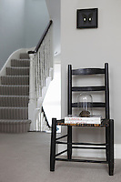 A simple ladder-backed chair occupies a space on the landing