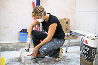 Student doing a course in tiling mixing the adhesive.  Able Skills in Dartford, Kent, runs courses in construction industry skills like, bricklaying, carpentry and tiling.