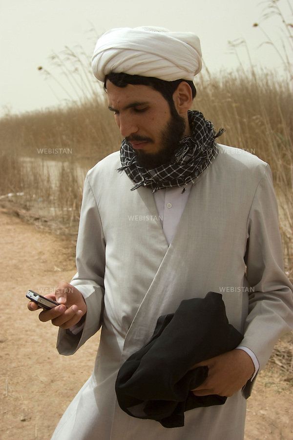Iran. Khuzistan province. March 22, 2009. Arvand Kenar. A mullah records recreated battle sound with his cell phone near the remains of Iran-Iraq War (1980-1988) frontline zone, close to the Iraqi border. Every year, during the celebration of Nowrooz, the Iranian new year, thousands of Iranians from all over the country, called &quot;Rahian-e Noor&quot; (Caravan of light in Persian), helped by state organizations, gather on former battle fields to commemorate their loved ones who died as soldiers or Basijis. All expenses of this pilgrimage being paid by the State, makes it a favored touristic destination for  families of humble background. The Iran-Iraq War was one of the deadliest armed conflicts of the last quarter of the twentieth century, leaving one million victims.<br />