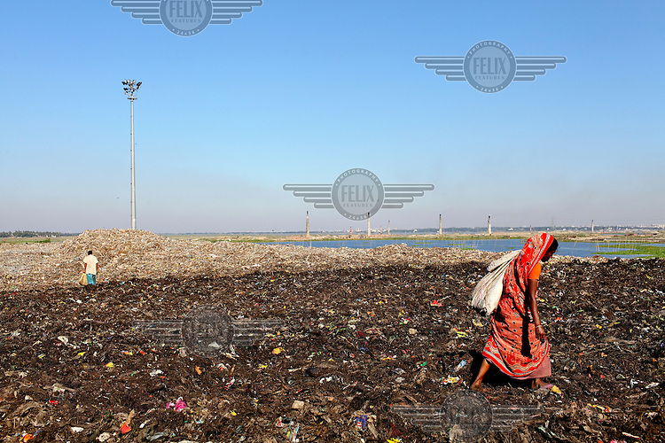 A woman looks for recyclable material at the biggest rubbish dump in Dhaka. The city alone generates about 3500 to 4000 metric tons of solid waste each day.