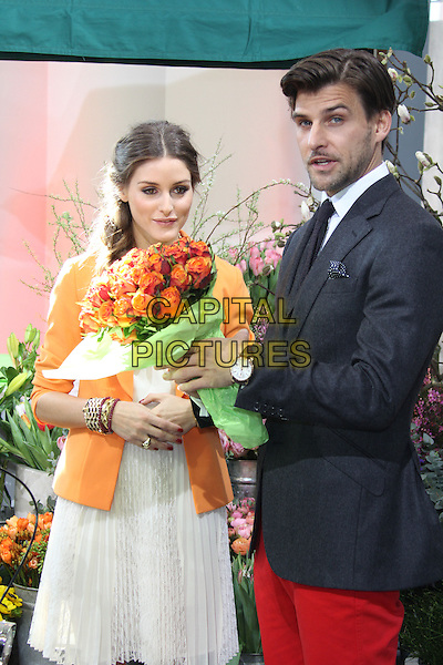 "Olivia Palermo & Johannes Huebl.Photocall for the new faces of ""OTTO""-group (online seller) presenting duos Oliva Palermo and partner Johannes Huebl, location ""Prototype"", Hamburg, Germany..March 5th, 2013.half length jacket red necklace gold dress red jeans trousers couple orange blazer braid plait hair loose white shirt mouth open flowers bouquet side funny  blue knitted tie grey gray suit stubble facial hair .CAP/UNT.©Unit2/Capital Pictures"