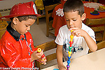 Preschool 4-5 year olds identical twin brothers playing with peg toys making towers using opposite hands