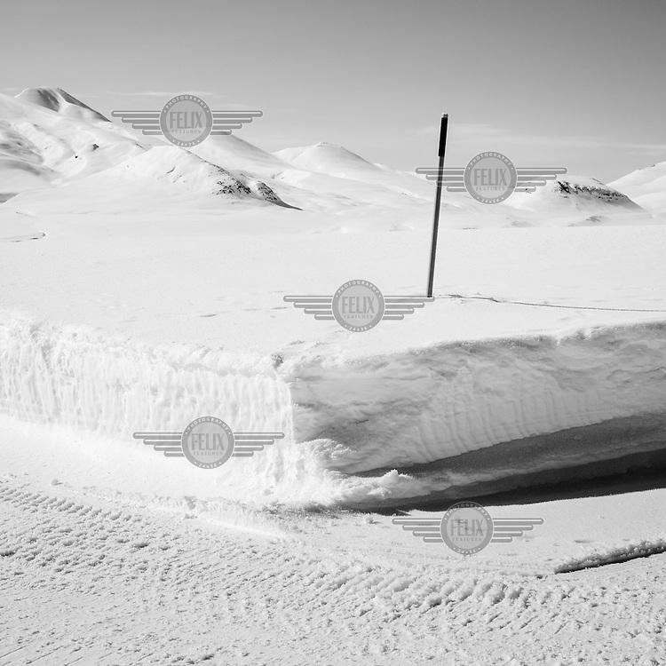 A road sign sticks out of the deep snow alongside a road in Mestersvig. Mestersvig is a military outpost with a runaway in the Scoresby Land region of the Northeast Greenland National Park. Originally built in anticipation of mining in the area it has been run by the Danish defence department since 1988. The place is staffed by two men whose duties include maintenance of buildings and the airfield and support of other activities in the area.