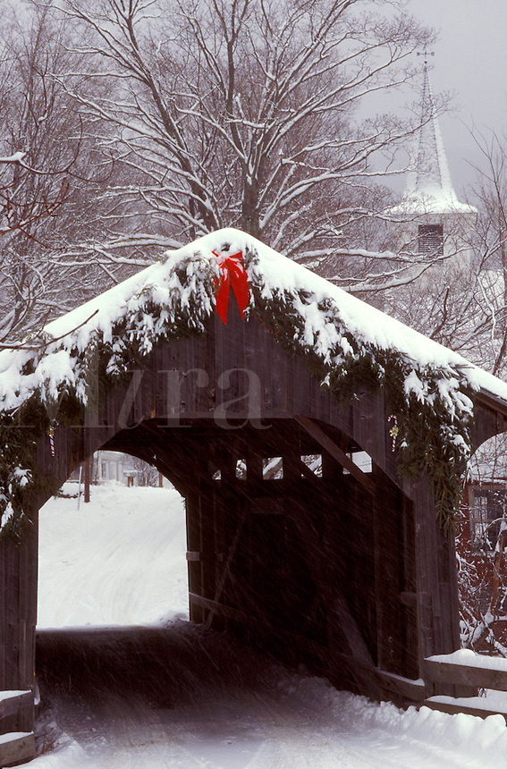 AJ1090, Vermont, covered bridge, The snow covered Village or Church Street Covered Bridge, circa 1877, is decorated for the Christmas holidays with greens and a red bow. A New England style church stands in the background in Waterville.