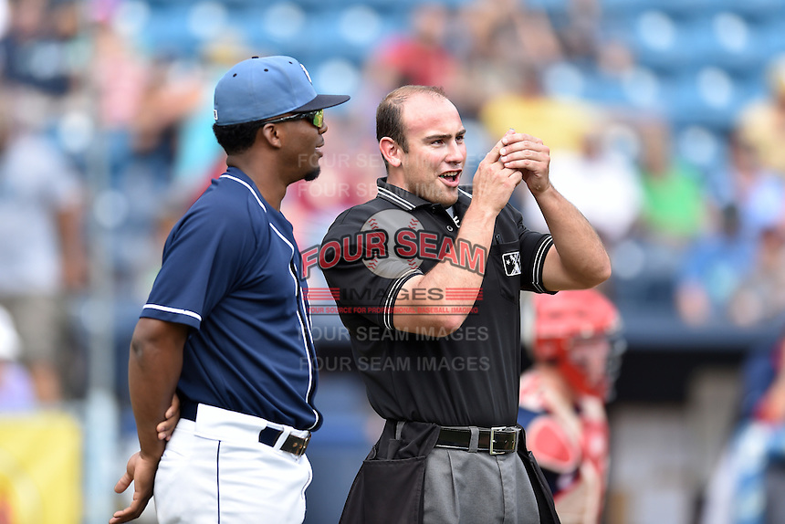 Asheville Tourists player Terry McClure (5) take contact solution to home plate umpire Jason Johnson during a game against the Hagerstown Suns at McCormick Field on September 5, 2016 in Asheville, North Carolina. The Suns defeated the Tourists 9-5. (Tony Farlow/Four Seam Images)