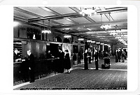 Lobby, photograph, 1960s, from the Archives of the Chateau Frontenac, Quebec City, Quebec, Canada. The Chateau Frontenac opened in 1893 and was designed by Bruce Price as a chateau style hotel for the Canadian Pacific Railway company or CPR. It was extended in 1924 by William Sutherland Maxwell. The building is now a hotel, the Fairmont Le Chateau Frontenac, and is listed as a National Historic Site of Canada. The Historic District of Old Quebec is listed as a UNESCO World Heritage Site. Copyright Archives Chateau Frontenac / Manuel Cohen