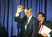 Washington, D.C. - June 25, 1990 -- Nelson Mandela, leader of the African National Congress (ANC) waves to the media as he arrives to conduct a press conference after meeting with United States President George H.W. Bush at the White House on Monday, June 25, 1990.  The aide at right is unidentified..Credit: Ron Sachs / CNP