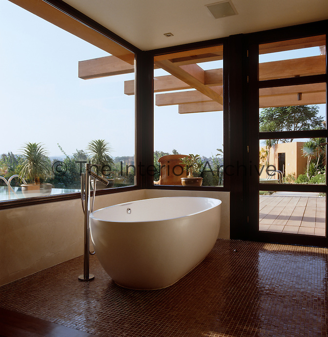 Overlooking the outdoor swimming pool, the glassed-in bathroom has an oval-shaped bath and a mosaic-tiled floor