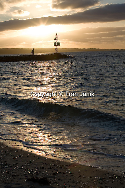 Waves lap on the shore in the foreground as two people are seen standing on a stone Jetty  silouetted by the sun breaking through the clouds as it sets.