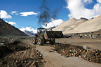"A bulldozer belches smoke as it clears a road to everest base camp.<br /> China started building a controversial 67-mile ""paved highway fenced with undulating guardrails"" to Mount Qomolangma, known in the west as Mount Everest, to help facilitate next year's Olympic Games torch relay."