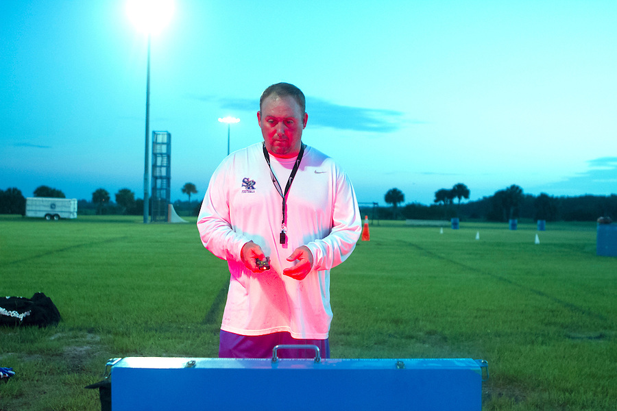 MAE GAMMINO/SPECIAL TO SCRIPPS TREASURE COAST NEWSPAPERS<br /> <br /> Sebastian River High School's new Varsity Football Coach Kevin Pettis programs the game clock on Monday morning before his team takes the field on the first day of practice at 6 a.m.  Today marks the beginning of a two week training camp-like approach to practice intended to begin the building process for a strong and cohesive team before regular football season.