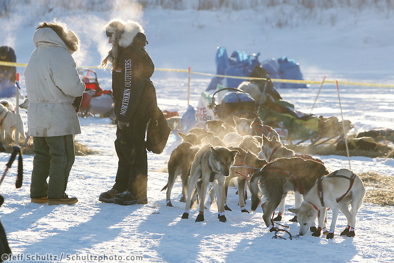 Former Iditarod musher John Cooper (L) talks with Kristy Berington as she prepares to leave the ghost-town checkpoint of Iditarod as the sun rises on Friday morning during the 2011 Iditarod race..