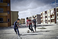 EGYPT, 6 of October City: Ali, Youssef and Mohamed are playing football in front of their home. Their father don't let them to go further scared that they get annoyed or harrassed by Egyptians.  27th January 2014<br /> <br /> EGYPTE, ville du 6 octobre: Ali, Youssef et Mohammed jouent au football en face de leur maison. Leur p&egrave;re ne les laisse pas &agrave; aller plus loin de peur qu'ils se fassent aggresser par des Egyptiens. 27th Janvier 2014