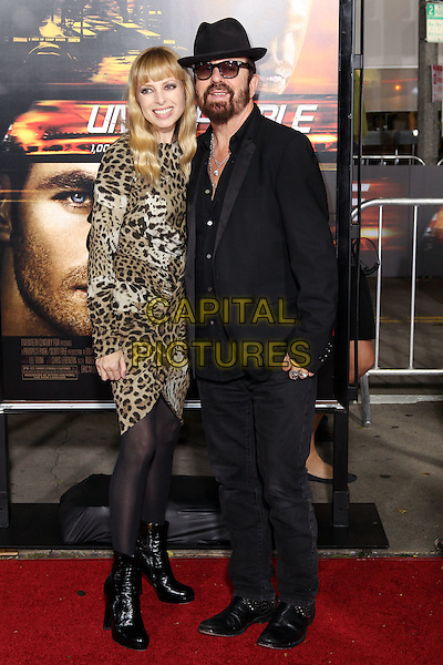 """ANOUSHKA FISZ, DAVE STEWART..Twentieth Century Fox world premiere of Tony Scott's action-thriller, """"Unstoppable,"""" at the Regency Village Theater in Westwood. Los Angeles, CA, USA, October 26th, 2010. .full length black suit hat couple leopard animal brown print dress long sleeve tights ankle boots  Anoushaka.CAP/CEL.©CelPh/Capital Pictures."""