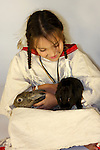 A young Native American Indian girl holding two bunny rabbits