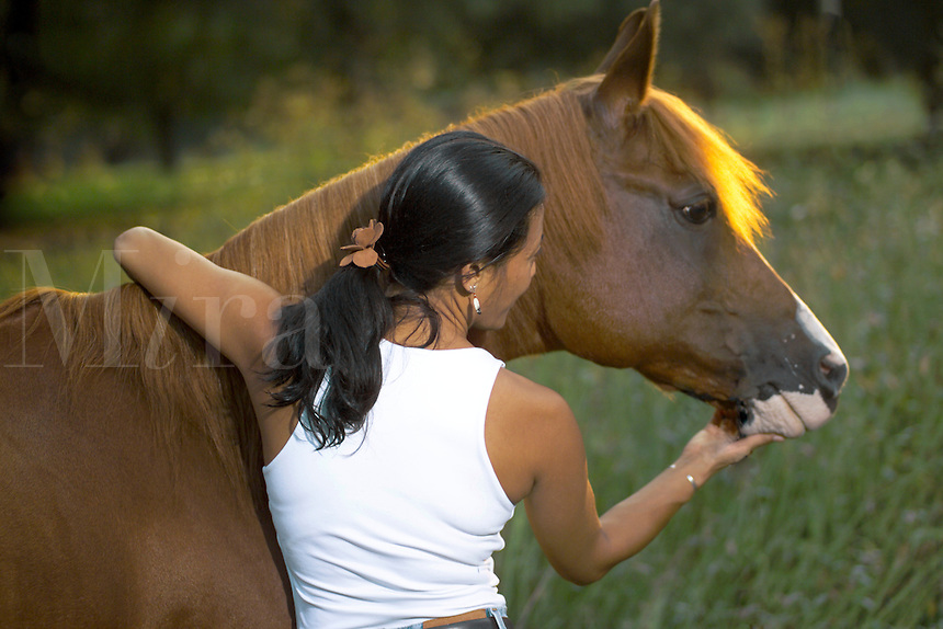 Young woman caresses muzzle of her horse.