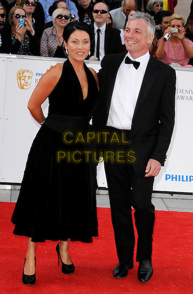 JESSIE WALLACE & GUEST .Attending the Philips British Academy Television Awards, Grosvenor house Hotel, Park Lane, London, England, UK, May 22nd 2011..arrivals TV Baftas Bafta full length black dress tuxedo white shirt bow tie halterneck .CAP/CAN.©Can Nguyen/Capital Pictures.