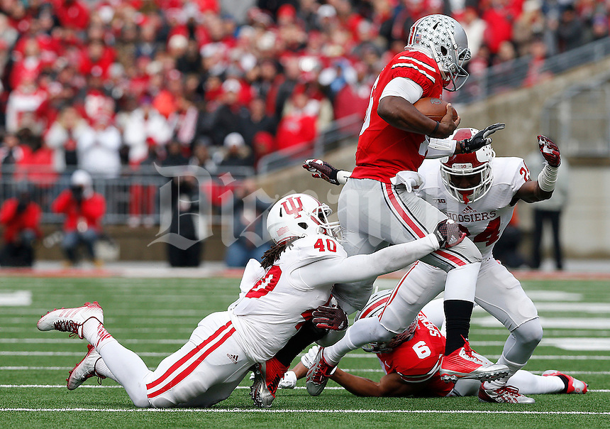 Ohio State Buckeyes quarterback J.T. Barrett (16) is tackled by Indiana Hoosiers safety Antonio Allen (40) in the second quarter of their game at Ohio Stadium in Columbus, Ohio on November 22, 2014. (Columbus Dispatch photo by Brooke LaValley)