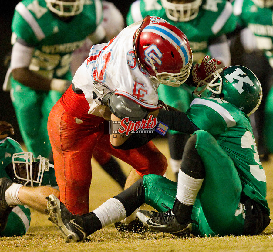 Steven Bevilacqua (32) of the Charlotte Catholic Cougars is wrestled to the ground by JP Lott (33) of the A.L. Brown Wonders at A.L. Brown High School on November 26, 2010 in Kannapolis, North Carolina.  The Cougars defeated the Wonders 45-7.  (Brian Westerholt/Sports On Film)