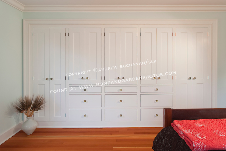 a solid wall of builtin storage cabinets and warm fir floors in the second