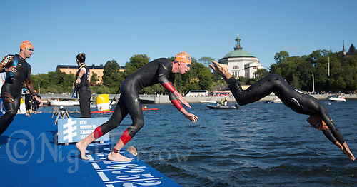 25 AUG 2013 - STOCKHOLM, SWE - Competitors dive off the pontoon for the start of their second swim lap during the men's ITU 2013 World Triathlon Series round in Gamla Stan, Stockholm, Sweden (PHOTO COPYRIGHT © 2013 NIGEL FARROW, ALL RIGHTS RESERVED)