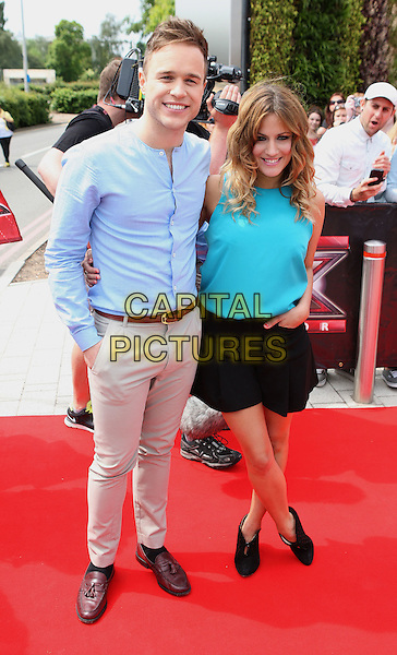 OLLY MURS & CAROLINE FLACK .New X Factor Judges arrive at auditions for the show at LG Arena, Birmingham, England, June 1st 2011..full length blue shirt turquoise top black shorts  ankle boots shooboots beige trousers belt hand in pocket xtra factor preseters brown loafers .CAP/ROS.©Steve Ross/Capital Pictures