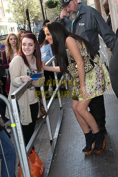 Tulisa Contostavlos at the studios of BBC Radio 1, London, England..April 2nd, 2012.full length yellow purple red floral print dress leopard print bag purse black ankle boots shoes wood wooden heel platform fans crouching profile  .CAP/HIL.©John Hillcoat/Capital Pictures .